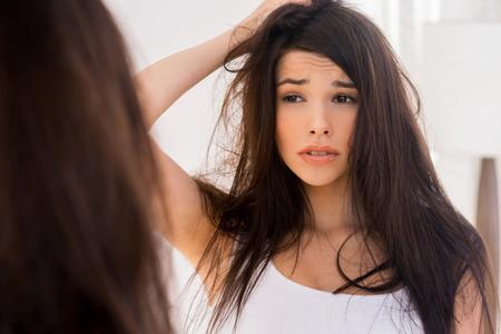 groviglio: Buongiorno? Frustrato giovane donna guardando il suo riflesso nello specchio e tenendo la mano nei capelli