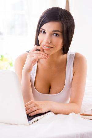 net surfing: Navigare in rete a letto. Bella giovane sorridente donna con laptop mentre giaceva a letto