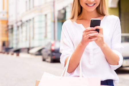 mobile shopping: Telling friend about sales. Close-up of beautiful young smiling woman holding shopping bags and mobile phone while standing outdoors