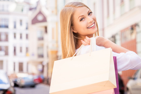 over the shoulder view: Nice day for shopping. Rear view of beautiful young cheerful woman holding shopping bags and looking over shoulder while standing outdoors