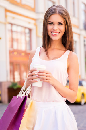 refreshed: Getting refreshed after day shopping. Beautiful young smiling woman holding shopping bags and cup of hot drink while standing outdoors