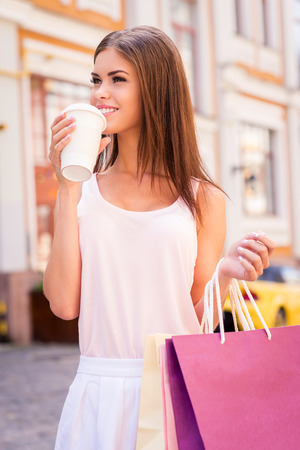 Relaxing after day shopping. Attractive young smiling woman holding shopping bags and drinking hot drink while standing outdoors photo