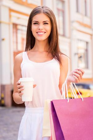 美しいお買いもの。ショッピング バッグやホットド リンクのカップを押しながら屋外で立って若い笑顔美人 写真素材