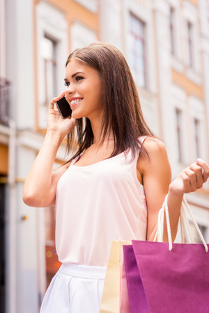 mobile shopping: Taking with friend about sales. Beautiful young smiling woman holding shopping bags and talking on the mobile phone while standing outdoors Stock Photo