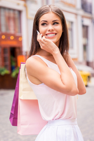 Taking about sales. Beautiful young smiling woman holding shopping bags and talking on the mobile phone while standing outdoors and looking over shoulder