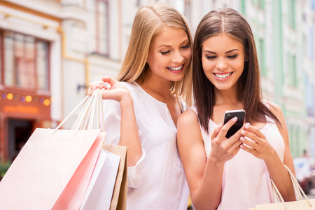 people in the street: Shopaholic friends. Two attractive young women holding shopping bags and looking at mobile phone together while standing outdoors Stock Photo