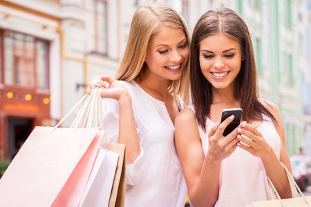Shopaholic vrienden. Twee aantrekkelijke jonge vrouwen die boodschappentassen en kijken naar de mobiele telefoon samen terwijl zich in openlucht