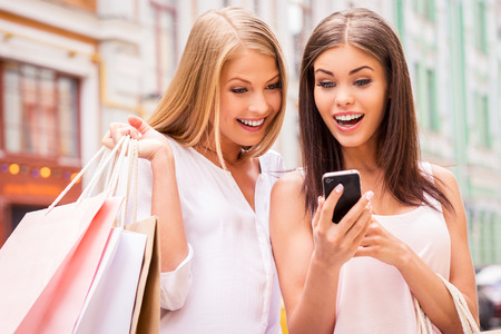 Can you imagine that? Two surprised young women holding shopping bags and looking at mobile phone together while standing outdoors Stock Photo