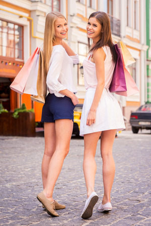 spending full: Friends shopping. Rear view of two beautiful young women holding shopping bags and looking over shoulder with smile while standing outdoors Stock Photo