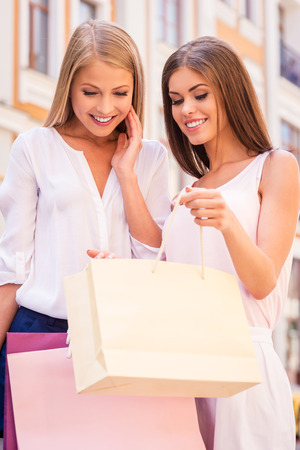 Look what I got! Beautiful young woman showing her friend what she got in her shopping bag while both standing outdoors  Stok Fotoğraf