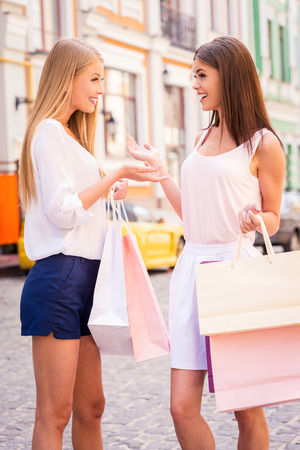 Friendly talk. Side view of two attractive young women talking while carrying shopping bags and standing outdoors