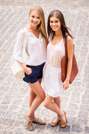 We are the best friends! Top view of two beautiful young women smiling at camera while standing close to each other outdoors