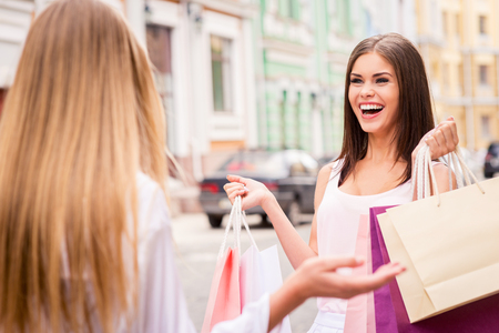Look what I got! Two young women with shopping bags standing face to face and gesturing
