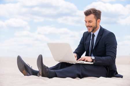 job satisfaction: Great place to work. Cheerful young man in formalwear working on laptop while sitting on sand in desert