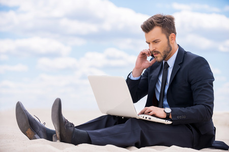 everywhere: Staying in touch anytime and everywhere. Confident young man in formalwear working on laptop and talking on mobile phone while sitting on sand in desert