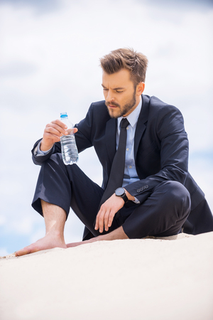 Water is life. Depressed young businessman holding bottle with water and looking at it while sitting on sand  photo