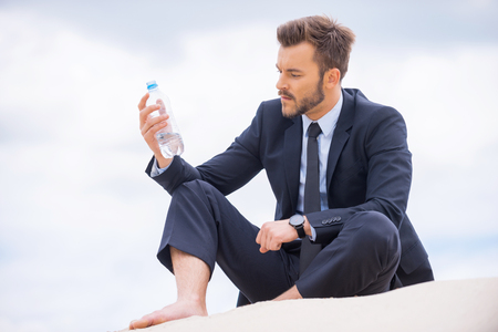 He needs to get refreshed. Depressed young businessman holding bottle with water and looking at it while sitting on sand  photo