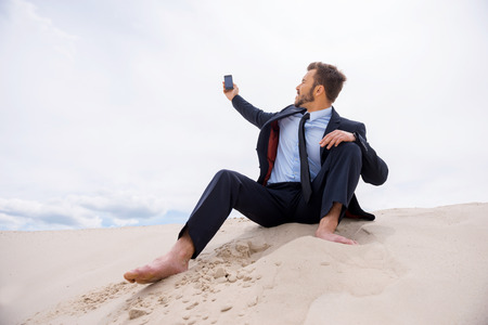Poor signal. Frustrated young businessman searching for mobile phone signal while sitting on sand in desert photo