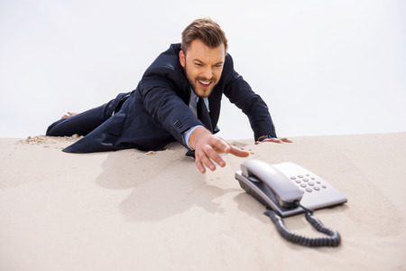 Urgent call. Young businessman stretching hand to telephone laying on sand  Stock Photo
