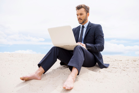Businessman in desert. Confident young man in formalwear working on laptop while sitting on sand in desert photo