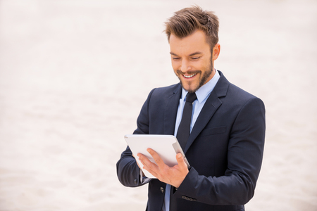 businessman standing: Surfing the net in desert. Cheerful young man in formalwear working on digital tablet while standing in desert Stock Photo