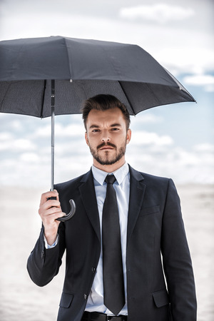 Businessman with umbrella. Confident young man in formalwear holding umbrella overhead while standing in desert  photo