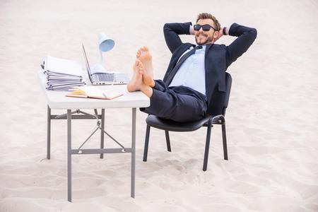 휴가를위한 준비. 잘 생긴 젊은 정장 남자와 선글라스를 머리 뒤로 손을 잡고 모래에 서 테이블에 그의 발을 들고 스톡 콘텐츠