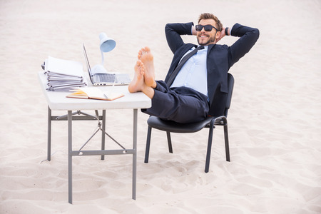 Ready for vacation. Handsome young man in formalwear and sunglasses holding hands behind head and holding his feet on the table standing on sand photo