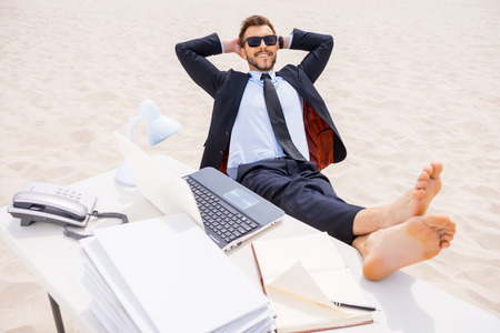 Total relaxation. Top view of relaxed young man in formalwear and sunglasses holding hands behind head and holding his feet on the table standing on sand