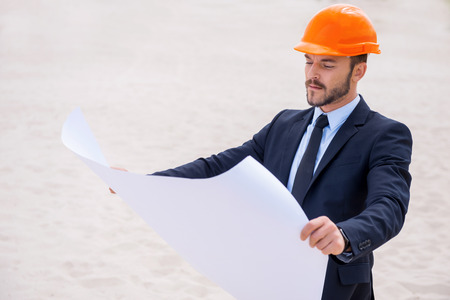 Architect with blueprint. Confident young man in formalwear and hardhat examining blueprint while standing on sand photo