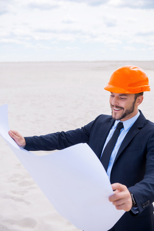 Inspired architect. Cheerful young man in formalwear and hardhat examining blueprint while standing in desert photo