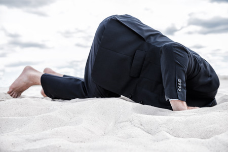 Hiding from his problems. Barefoot man in formalwear hiding his head in sand photo