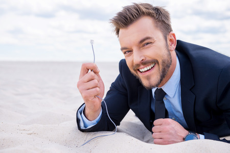 everywhere: Stay connected everywhere! Happy young smiling businessman looking at camera and holding network cable stretching out of sand