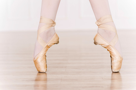 Elegance in every move. Close-up of ballerina legs in white tutu and slippers