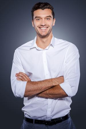 자신감 있고 성공적인. 회색 배경에 서있는 동안 카메라를 찾고 팔을 유지 흰 셔츠에 행복 젊은이 넘어 스톡 콘텐츠