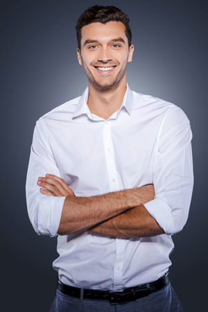 white shirt: Confident and successful. Happy young man in white shirt looking at camera and keeping arms crossed while standing against grey background Stock Photo
