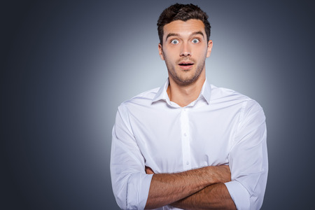 facial expressions: Wow! Surprised young man in white shirt staring at camera and keeping arms crossed while standing against grey background