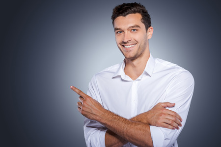 Handsome wijst kopie ruimte. Gelukkig jonge man in het witte shirt kijken naar de camera en glimlachen terwijl staande tegen de grijze achtergrond en wijzend kopie ruimte Stockfoto