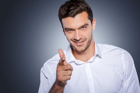 I choose you! Handsome young man in white shirt looking at camera and pointing you while standing against grey background
