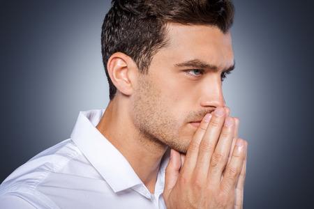 hombre orando: Concentrarse en? Vista lateral de la joven concentrada en la camisa blanca de la mano cerca de la cara entrelazadas y mirando de lejos mientras está de pie contra el fondo gris