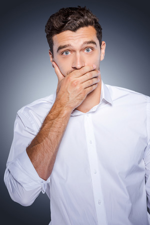 I will keep a secret! Surprised young man in white shirt covering mouth with hand and looking at camera while standing against grey background photo