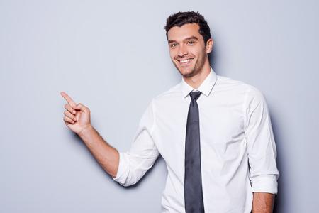 사업가 복사본 공간을 가리키는. 셔츠에 행복 한 젊은 남자와 카메라를 찾고 회색 배경에 서있는 동안 웃는 및 복사 공간을 가리키는 넥타이