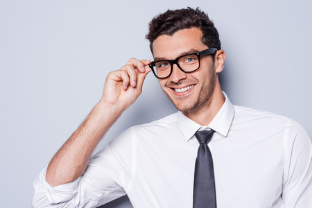 Zelfverzekerd en succesvol. Portret van de knappe jonge mens in overhemd en band die zijn oogglazen aanpassen en camera bekijken terwijl status tegen grijze achtergrond