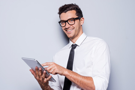 it background: Businessman with digital tablet. Handsome young man in shirt and tie working on digital tablet and smiling while standing against grey background Stock Photo