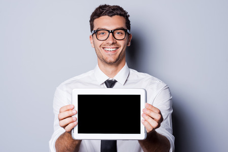 Copy space on his tablet. Handsome young man in shirt and tie showing his digital tablet and smiling while standing against grey background