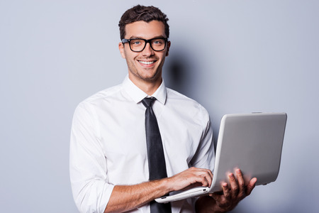 Confident IT expert. Handsome young man in shirt and tie working on laptop and smiling while standing against grey background Stock Photo