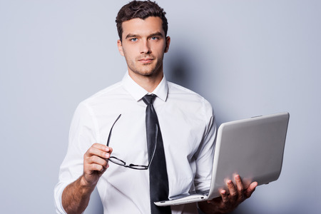 absolutely: You can absolutely trust me! Confident young man in shirt and tie holding laptop and eyeglasses while standing against grey background and looking at camera Stock Photo