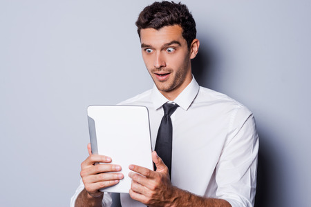 It is unbelievable! Surprised young man in shirt and tie\ looking at digital tablet and keeping mouth open while standing\ against grey background