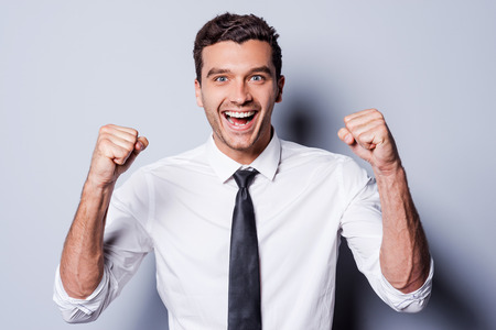 Successful businessman. Happy young man in shirt and tie gesturing and smiling while standing against grey background  Stok Fotoğraf