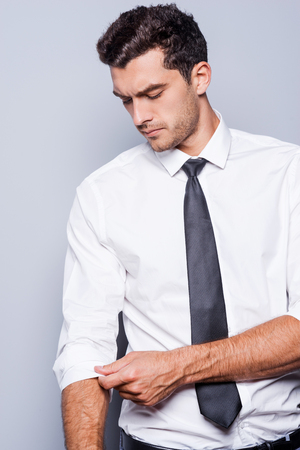 adjusting: Preparing to work. Handsome young man in shirt and tie adjusting his sleeve while standing against grey background